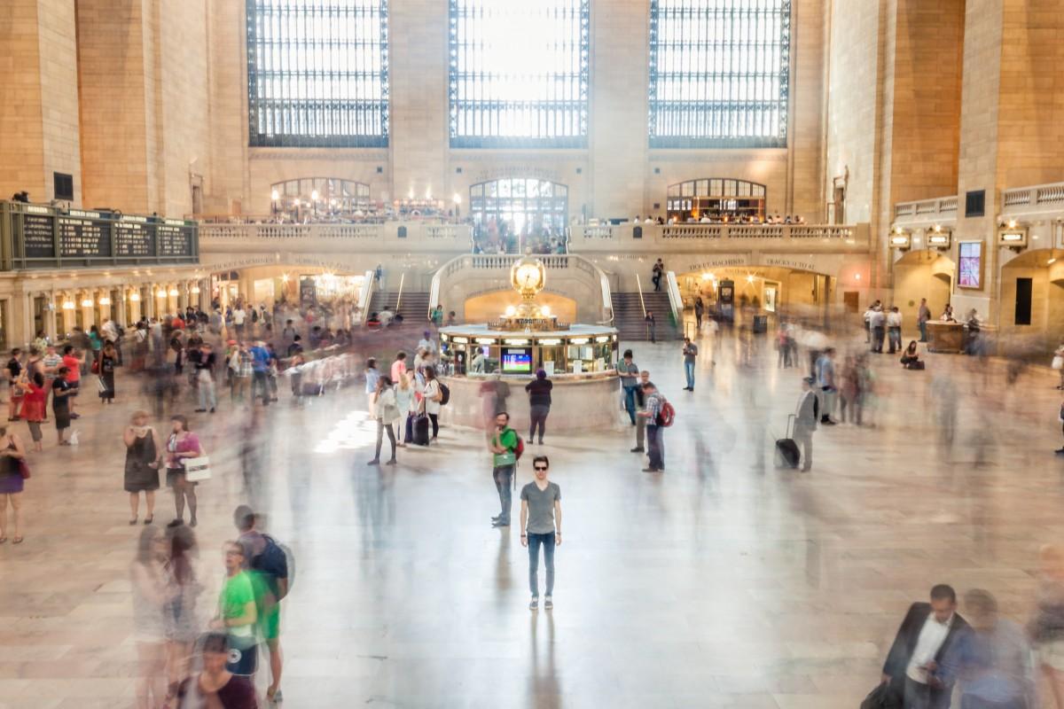 Ein Mann regungslos mitten in einer großen Bahnhofshalle, die Konturen zahlreicher anderer Personen verschwimmen, da diese offenbar in Bewegung sind